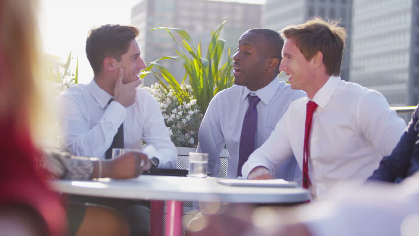 Cheerful mixed ethnicity business team in a meeting on a busy open air city roof terrace with views of the city skyline in the background. In slow motion.