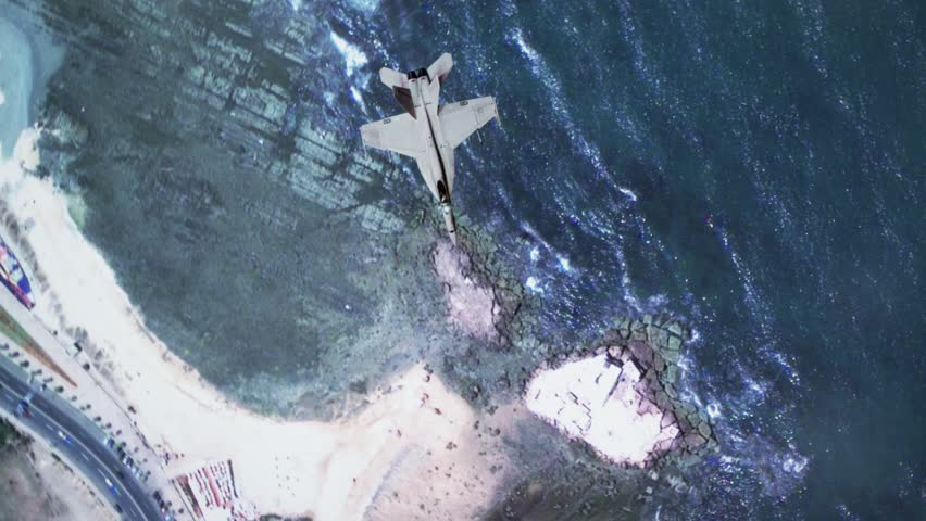 Overhead shot of F-18 Military Aircraft flying through clouds over land and water