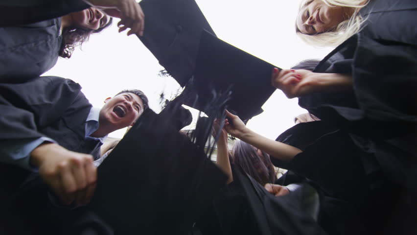 Graduation caps are tossed into the air by a happy group of student friends