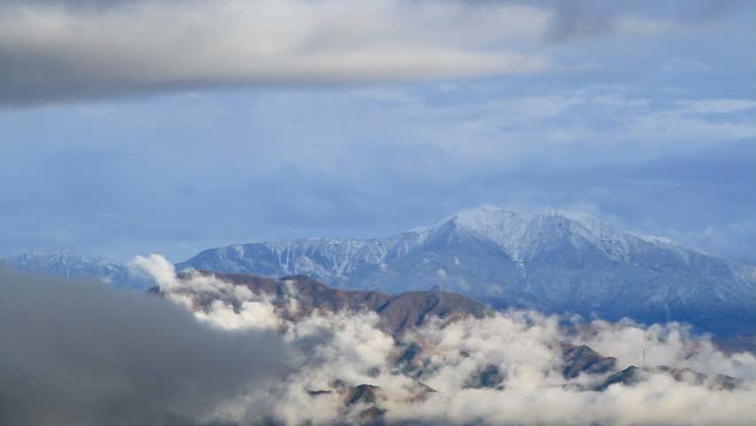 Cloud slides over the mountain range.
