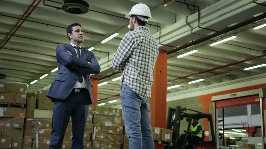 Adult Business Man In Logistics Facility Talking To Manual