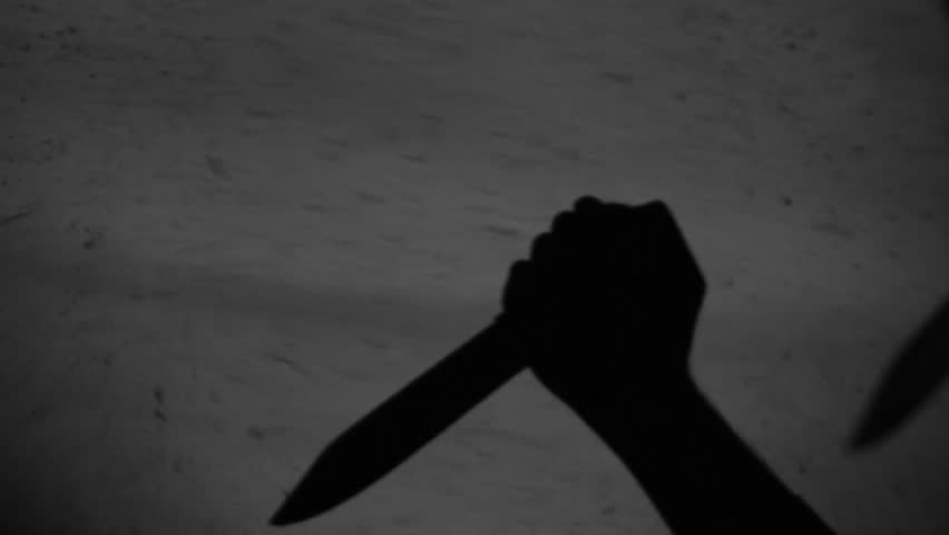 Shadow of a hand striking with a knife.