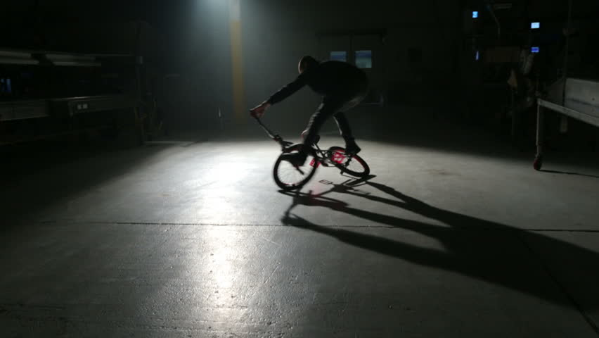 BMX rider doing tricks in dark warehouse - HD stock footage clip