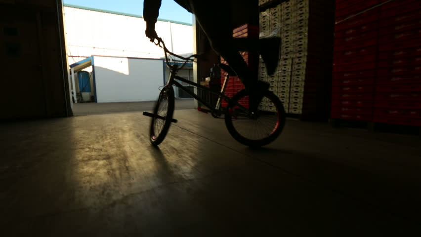 BMX rider doing tricks a commercial plant silhouetted  - HD stock footage clip
