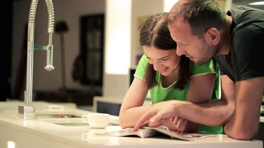 Couple in kitchen at home, chatting over magazine  - HD stock footage clip