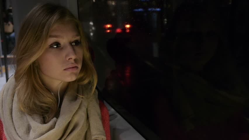 beautiful girl on a tram at night looking out the window