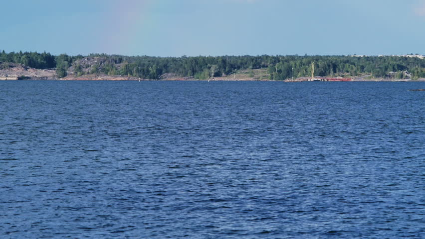 Rainbow over the islands near Helsinki, Finland. Warm summer day. Camera tilts up. - HD stock video clip