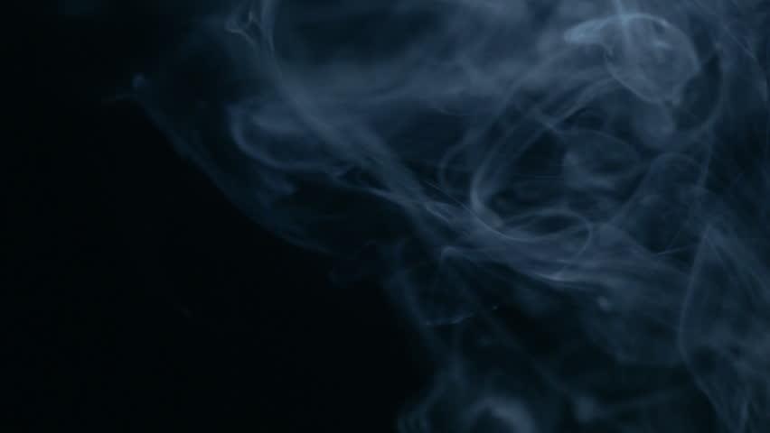 rising puff of white smoke on black background stock