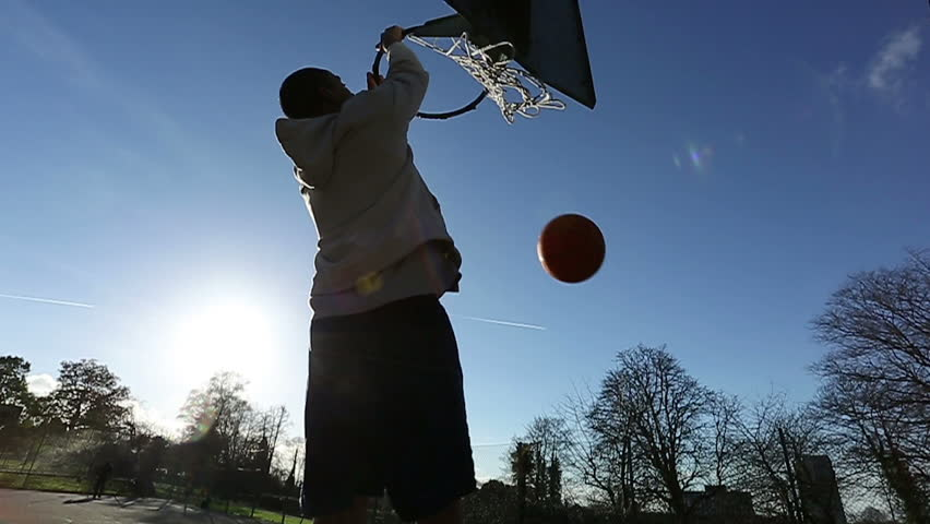 Basketball player slam dunking the ball on an outdoor basketball court - HD stock footage clip