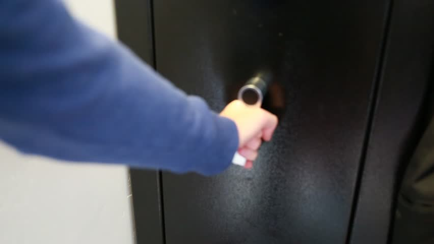 A man removes guns from a metal gun safe in his house