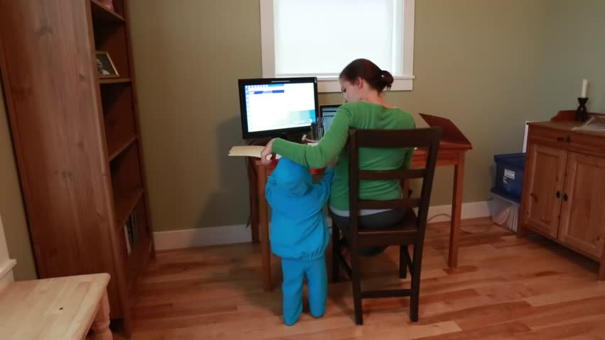 A working mother in a home office while her toddler plays in a monster outfit