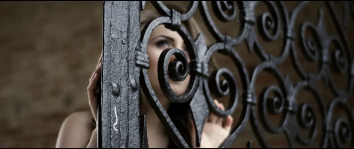 Beautiful bride in her wedding dress behind an iron gate