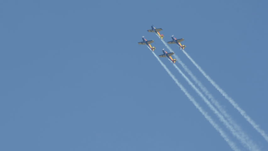 """CLUJ NAPOCA, ROMANIA - CIRCA OCTOBER 2013 -  Aerobatic planes do barrel roll in formation flying  """"Aeroclubul Roman""""    at Cluj Napoca Airport grand reopening airshow."""