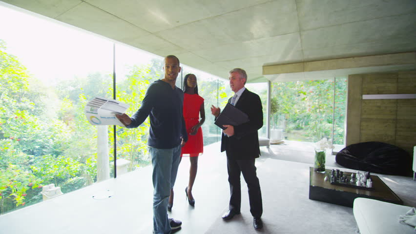Young couple being shown round a luxury modern home by the estate agent | Shutterstock HD Video #5233001