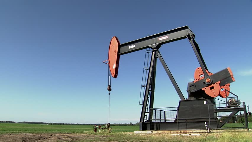 Oil rig pumping in Albertan countryside. (Pan Right) - HD stock video clip