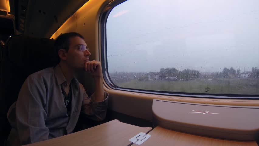 Man on the train looking at the landscape from the window - HD stock footage clip