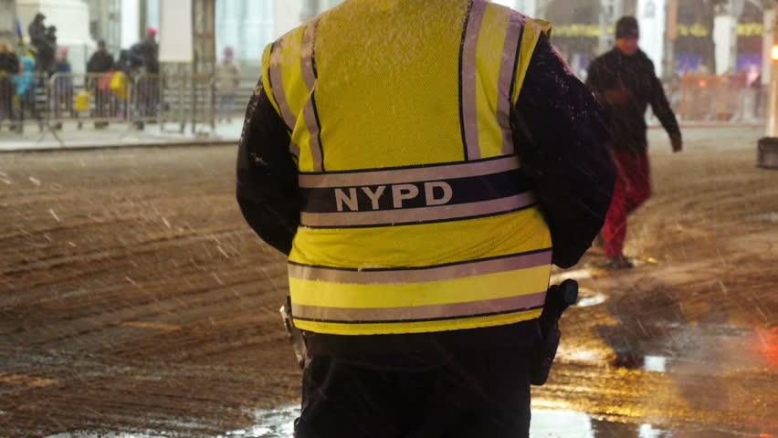 A New York City police officer helps guide traffic and pedestrians on the snowy