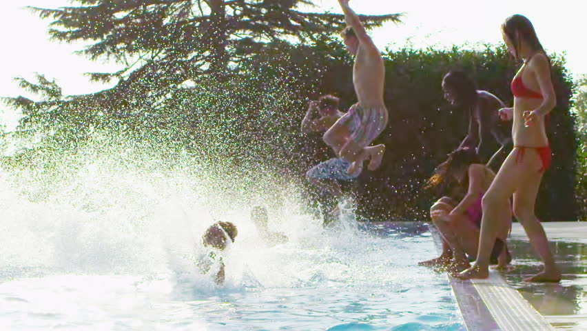 Happy fun loving group of friends jumping, splashing and playing in the swimming pool at a pool party. In slow motion. - HD stock footage clip