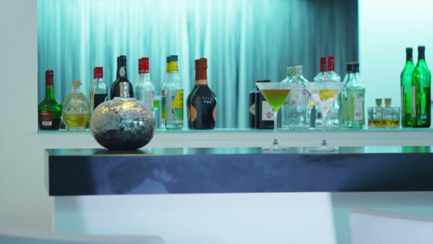 Bottles and glasses filled with colorful drinks in contemporary cocktail bar - no people. | Shutterstock HD Video #5261891