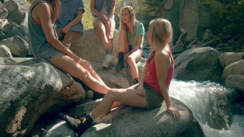 Group of Five Teenage Girls Sitting On Boulders Next To A Mountain Stream, Talking