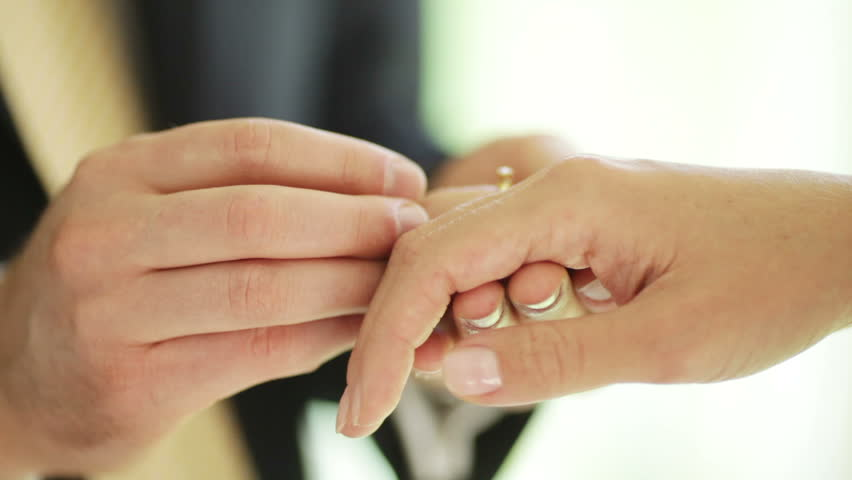 Gold Wedding Rings And Hands Of Just Married Couple Of Bride And Groom. People Get Married
