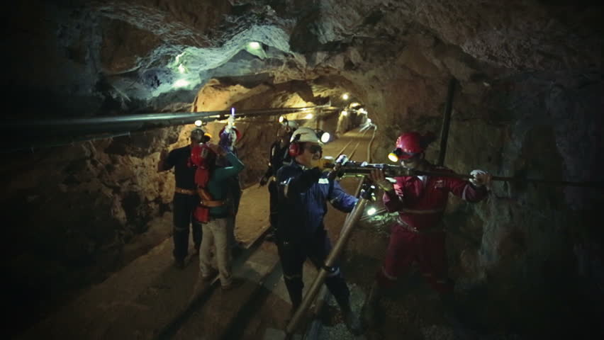 Engineers of mines and geology inside mine and workers perforating the rock using a pneumatic drill