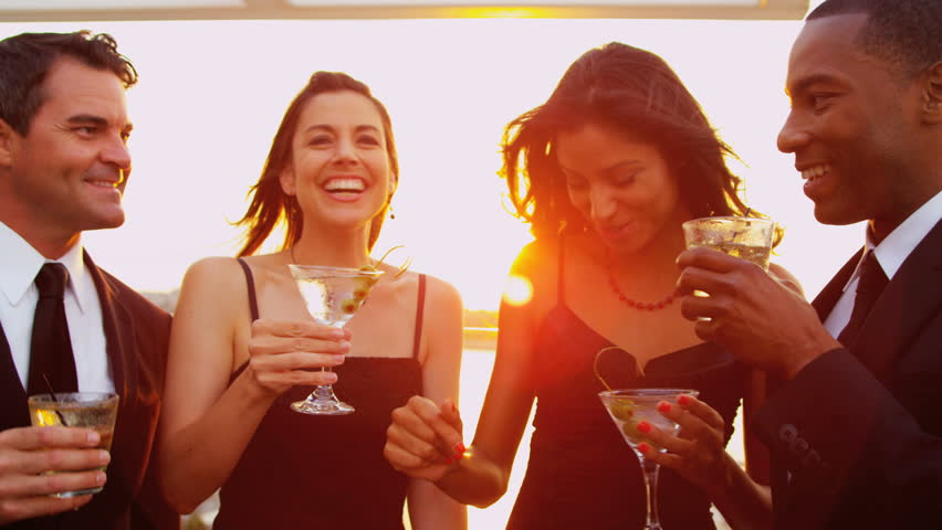 Smiling pretty diverse female and male friends enjoying cocktails and fun at city sunset party dressed in black shot on RED EPIC, 4K, UHD, Ultra HD resolution