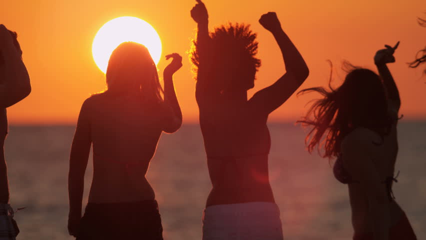 Multi ethnic male female young friends enjoying freedom college break dancing sunset coastal beach shot on RED EPIC, 4K, UHD, Ultra HD resolution