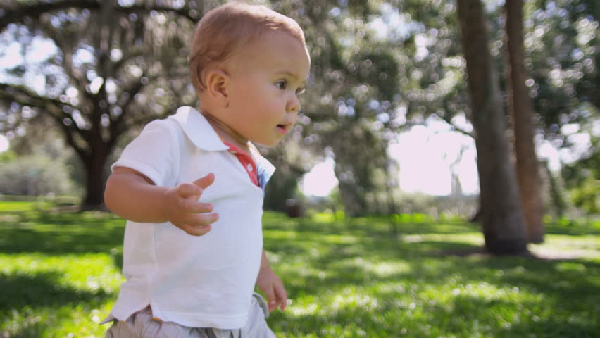 Cute little Caucasian male toddler child gaining confidence walking by himself sunny afternoon park slow motion shot on RED EPIC, 4K, UHD, Ultra HD resolution
