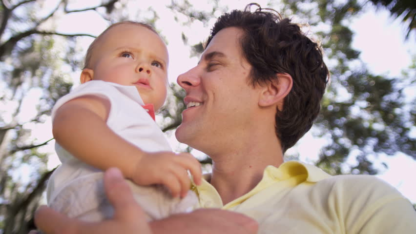Low angle close up young Caucasian father enjoying time outdoors park holding toddler son in his arms in sunshine sun lens flare shot on RED EPIC, 4K, UHD, Ultra HD resolution - 4K stock video clip