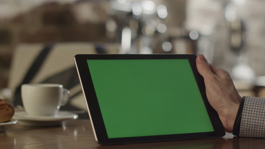 Man using Tablet in Coffee Shop. Tablet with Green Screen. Shot on RED Digital Cinema Camera in 4K, so you can easily crop and zoom, Great for presentation and mockups. Easy for tracking and keying.