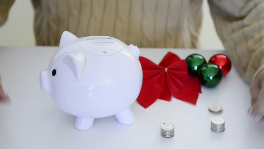 Hispanic man saving coins or money in a piggybank for Christmas. Saving money for Christmas.