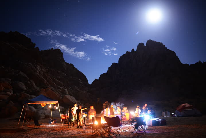 4K Time Lapse of People Enjoying Camping around Bonfire in Desert at Night