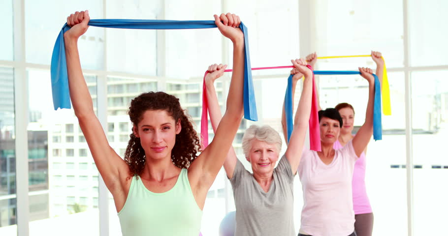Women stretching resitance bands at a fitness class at the gym