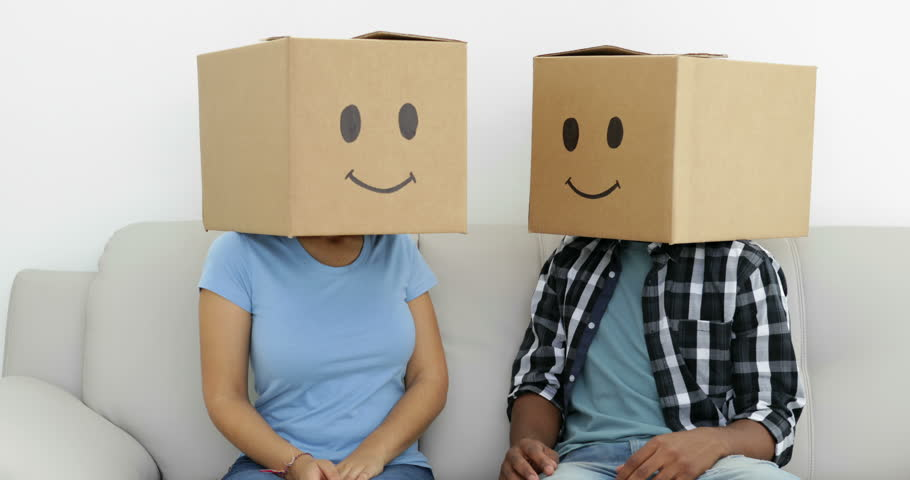 Silly employees with boxes on their heads in creative office