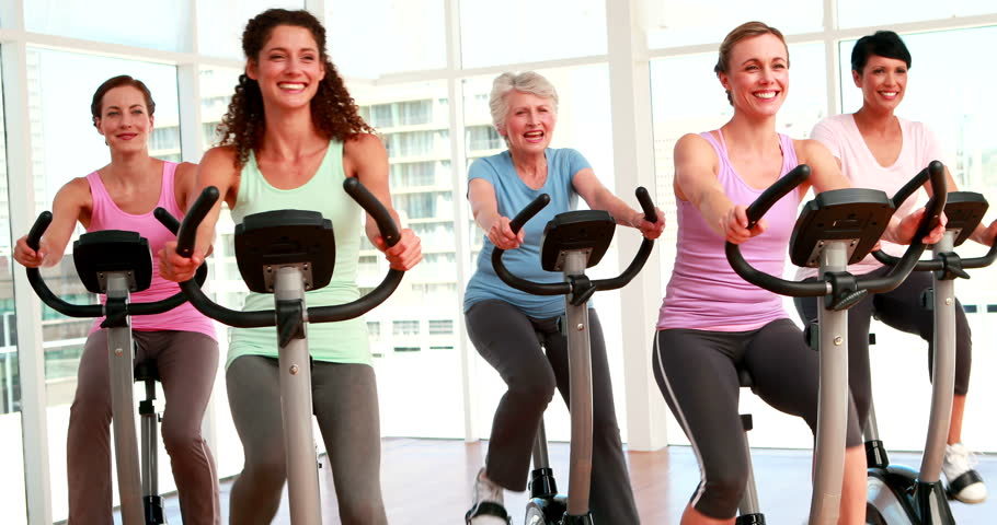 Group of smiling women in doing a spinning class at the gym - 4K stock footage clip