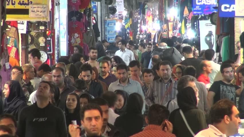 TEHRAN, IRAN - 9 OCTOBER 2013: Crowds walk through a colorful alley of the massive Tehran bazaar