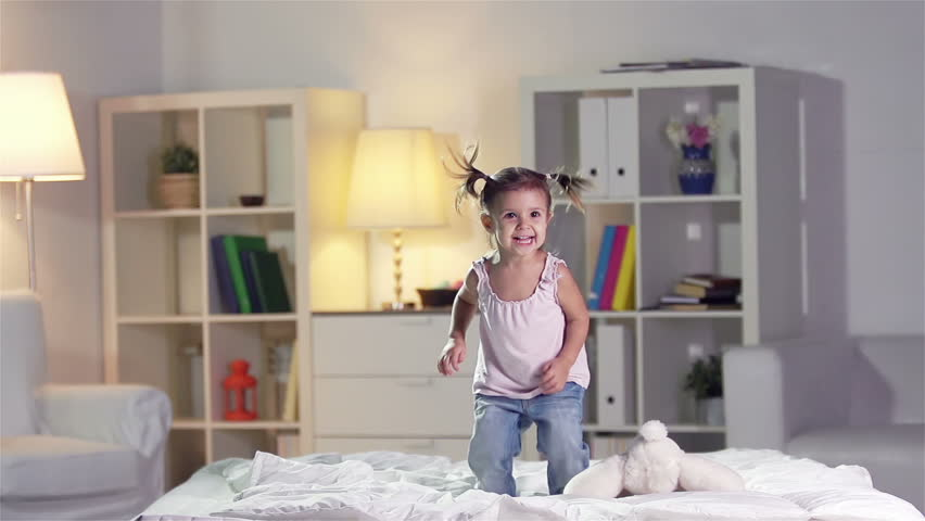 Slow-motion of a carefree girl jumping on the bed