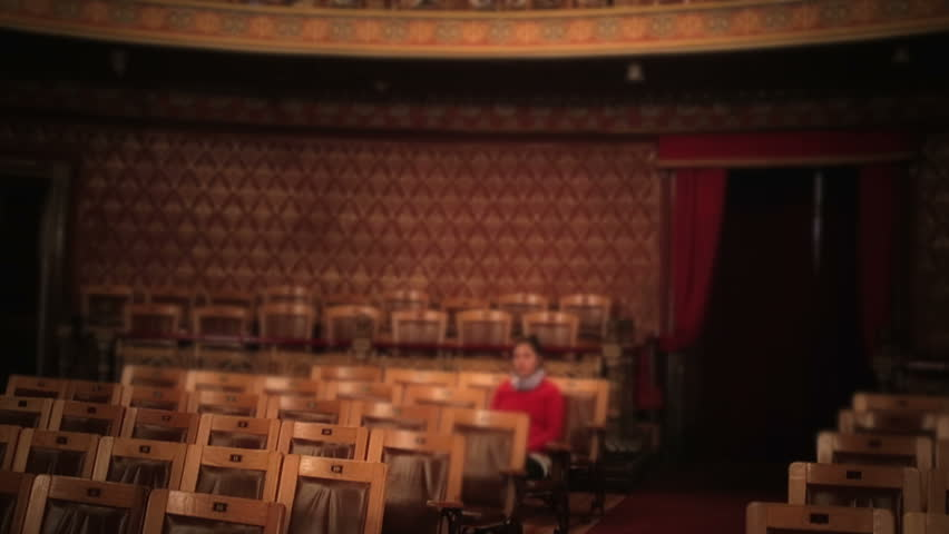 Person alone in theater, seated waiting for show - HD stock footage clip