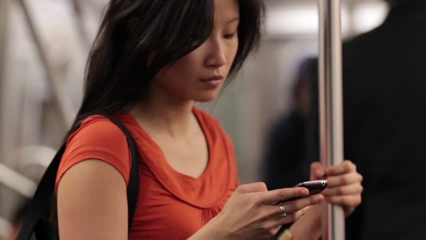 Woman Using Smart Phone in Subway - Standing