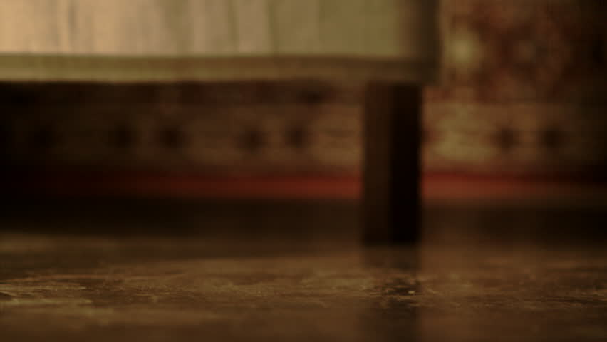 Slow motion view of a wineglass falling off a table and breaking into many pieces