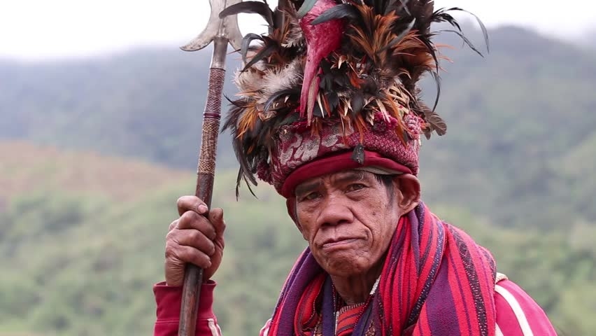 BANAUE - JANUARY 24 : Unknown old ifugao man in national dress next to rice terraces on January 24, 2014 in Banaue, Philippines. Ifugao - the people in the Philippines. Refers to the mountain peoples.