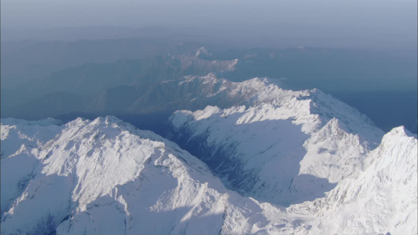 Peaks Snow Polar Rocky Mountains. A view from the top of snow covered mountain ranges. The rocky and sloping mountain ridges extend into a deep haze of clouds and fog. - HD stock footage clip