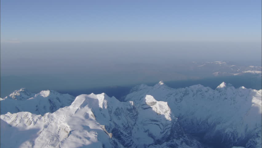 Peaks Snow Polar Rocky Mountains. A look from the top of a snow covered polar mountain range. The view of the smaller altitude ranges below are obscured by a thick haze. - HD stock video clip