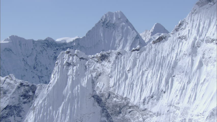 White Snow Rocky Mountains. Steep mountain ridges covered in white snow extend to a major mountain peak. Shallow jagged rocks line and create a narrow side to the face of the mountain.