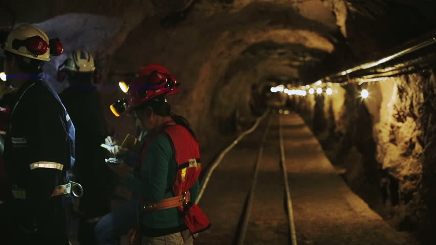 Engineers of geology and mining talking inside tunnel mine