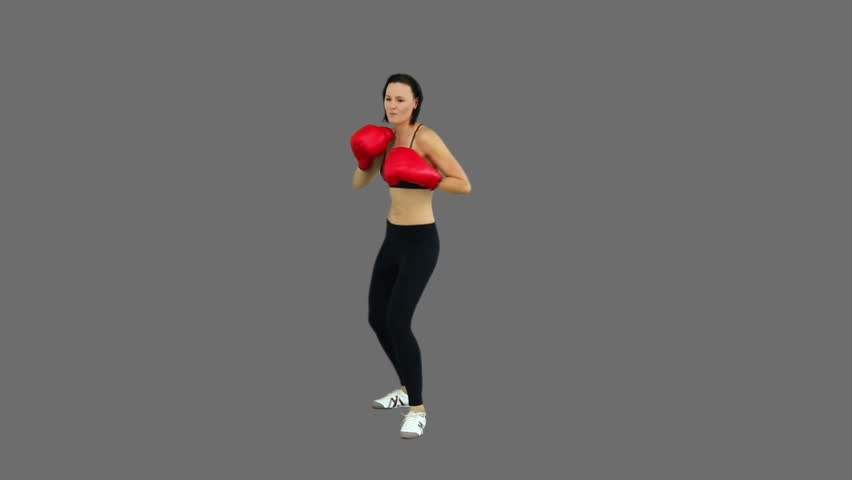 Fit brunette boxing with red gloves on grey screen background - HD stock footage clip