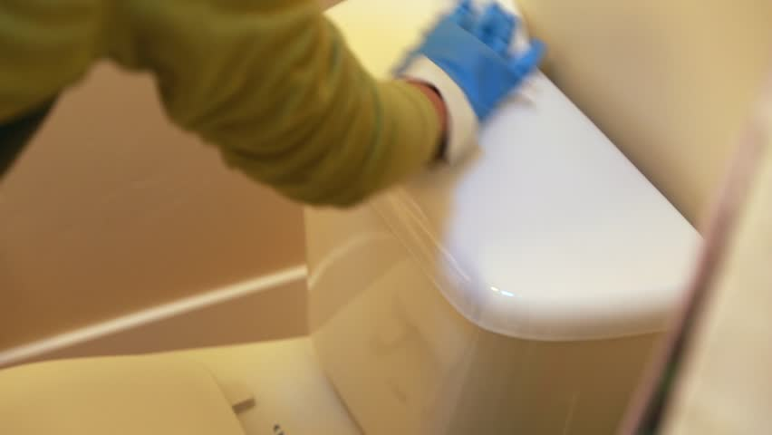 A woman cleaning the bathroom in her home