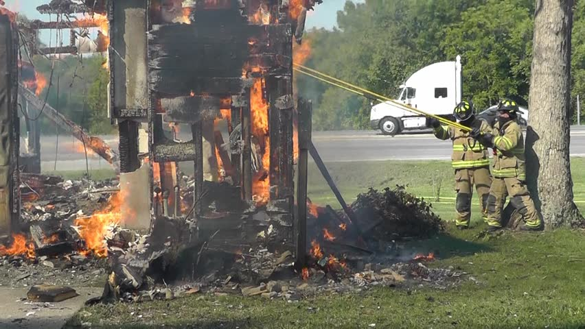 Firemen try to knock down a stubborn burning wall on a house fire is in it's last stages.