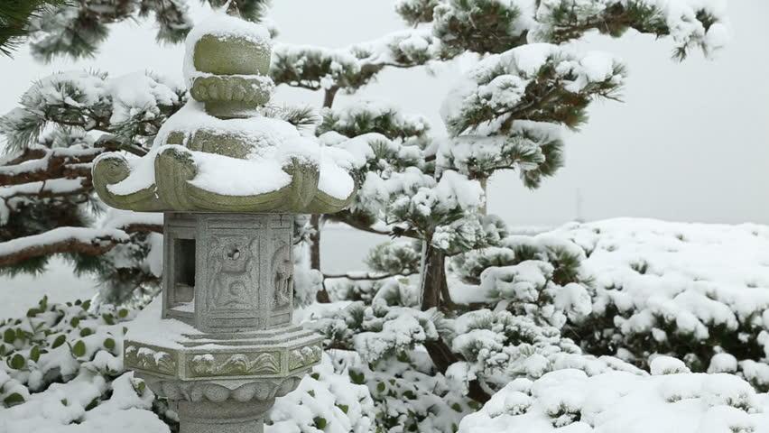 Stone Lantern Snow. Snow falling on a  Japanese stone lantern in a Japanese garden. - HD stock footage clip